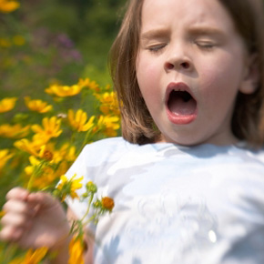 Young girl with flowers is sneezing, allergies